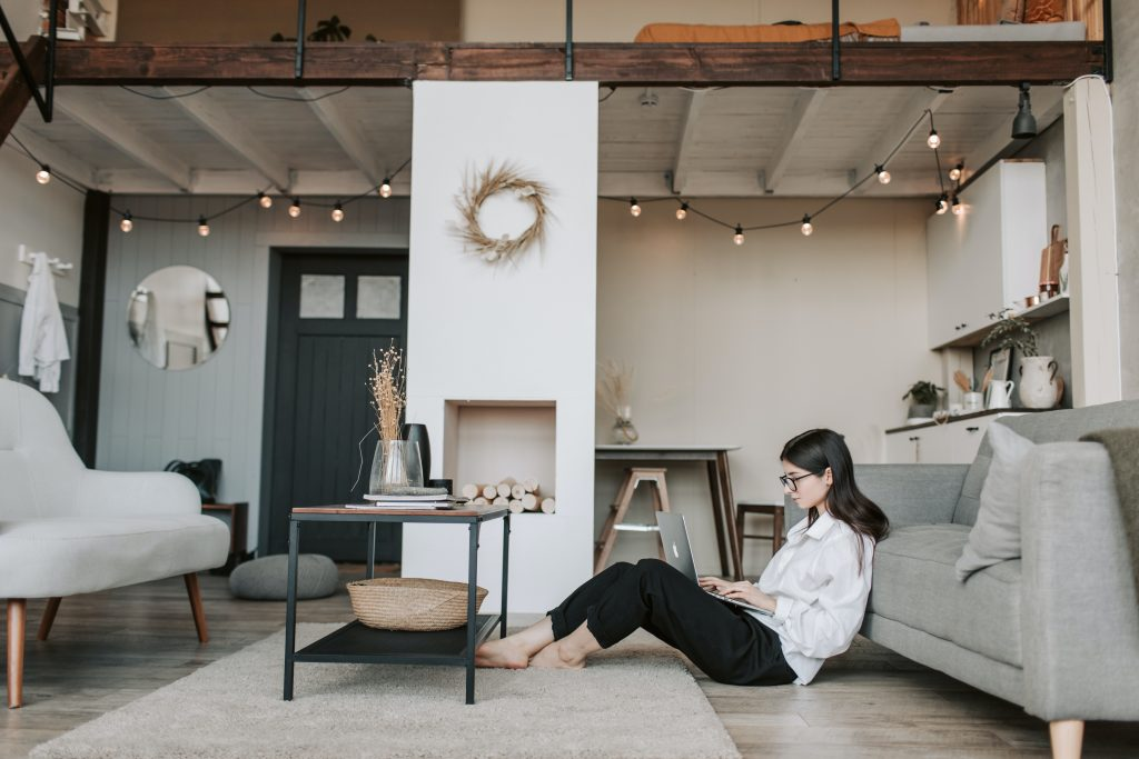 girl on the floor with a laptop in condo living room