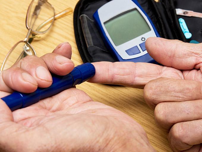 Mit einer Lanzette entnimmt man Blut aus dem Finger, um mithilfe des danebenliegenden Blutzuckermessgeräts den Nüchternblutzuckerwert zu ermitteln.
