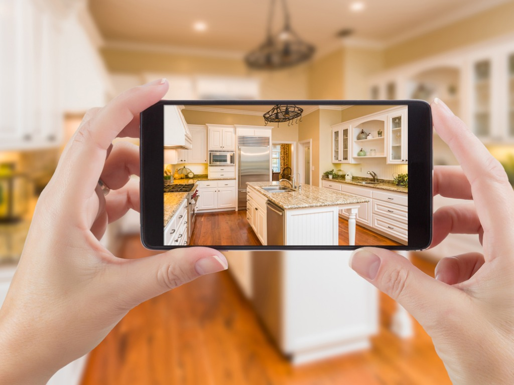 hands holding smartphone taking picture of clean nice kitchen