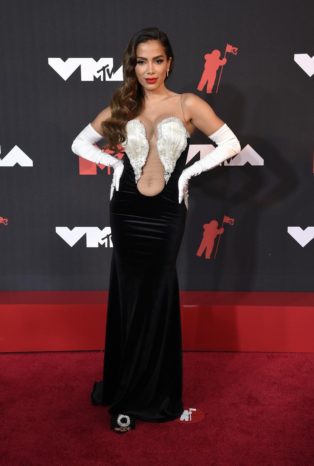 Mulher branca está de pé no tapete vermelho, tem cabelo escuro solto, com vestido preto e detalhes em branco no busto, além de usar luvas compridas brancas, está de sapatos pretos. Foto: Evan Agostini/Invision/AP. Post Looks icônicos do VMA e Met Gala 2021.