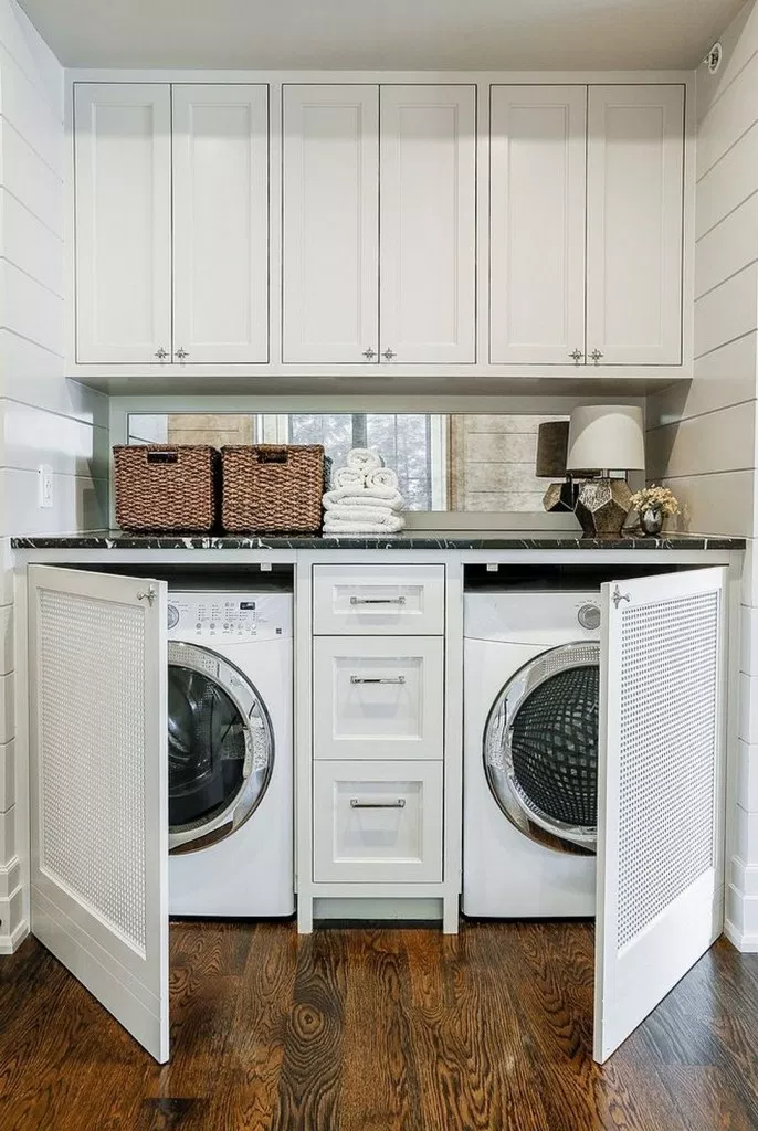 small white laundry room with white shaker cabinets. the washer and dryer are hidden behind custom cabinet doors