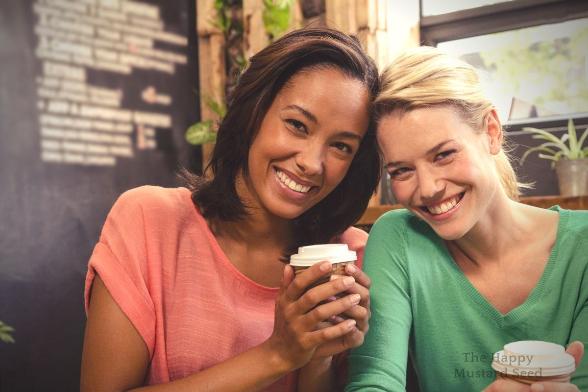 Black mom and White Mom Smiling and having coffee