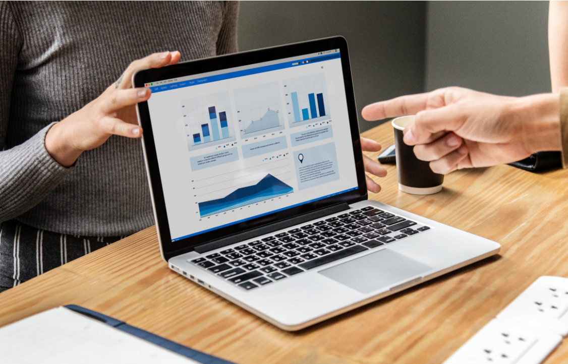Two people pointing to laptop with UX ROI charts