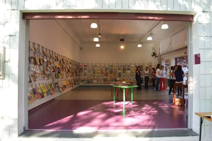 A imagem mostra uma sala. Em duas paredes da sala, varais sustentam uma exposição de livros.