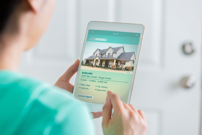 A woman browsing through house listings on her iPad