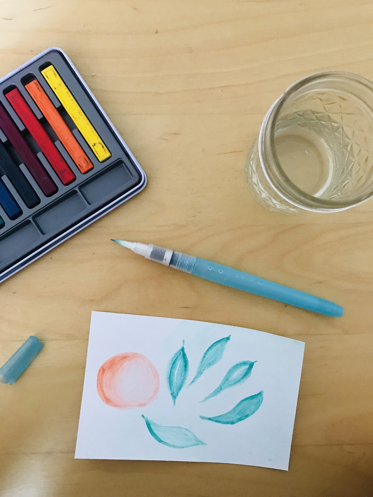 Photo of an abstract watercolor drawing and art supplies.