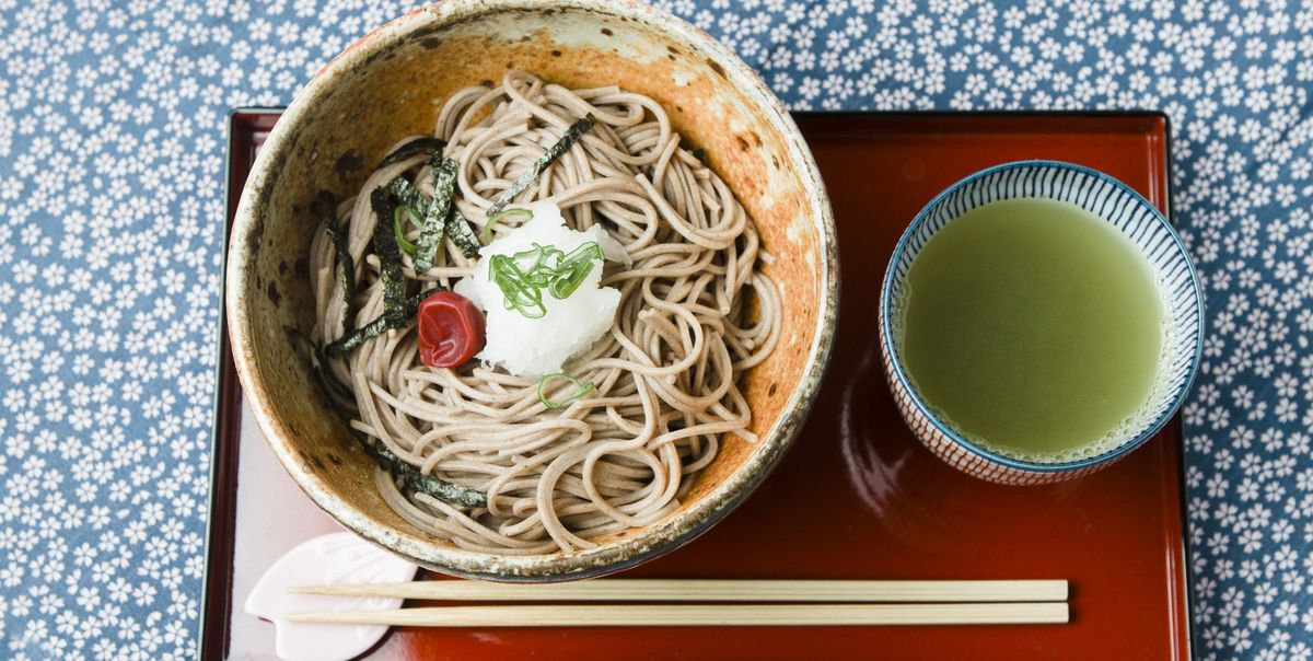 Soba noodles in a bowl with chopsticks and broth on the side