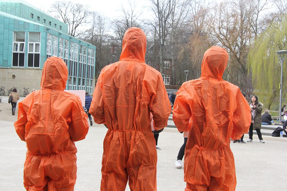 Three people wearing biohazard suits on the science site