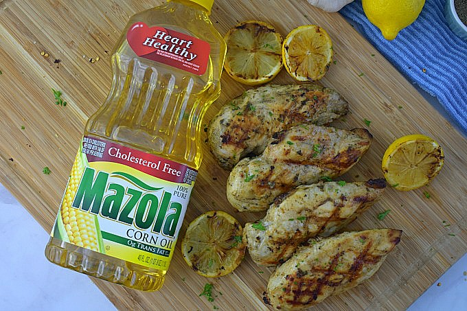 A bottle of Mazola Corn Oil on a cutting board surrounded by grilled lemon garlic chicken and grilled lemons. The oil is used to make a chicken marinade.