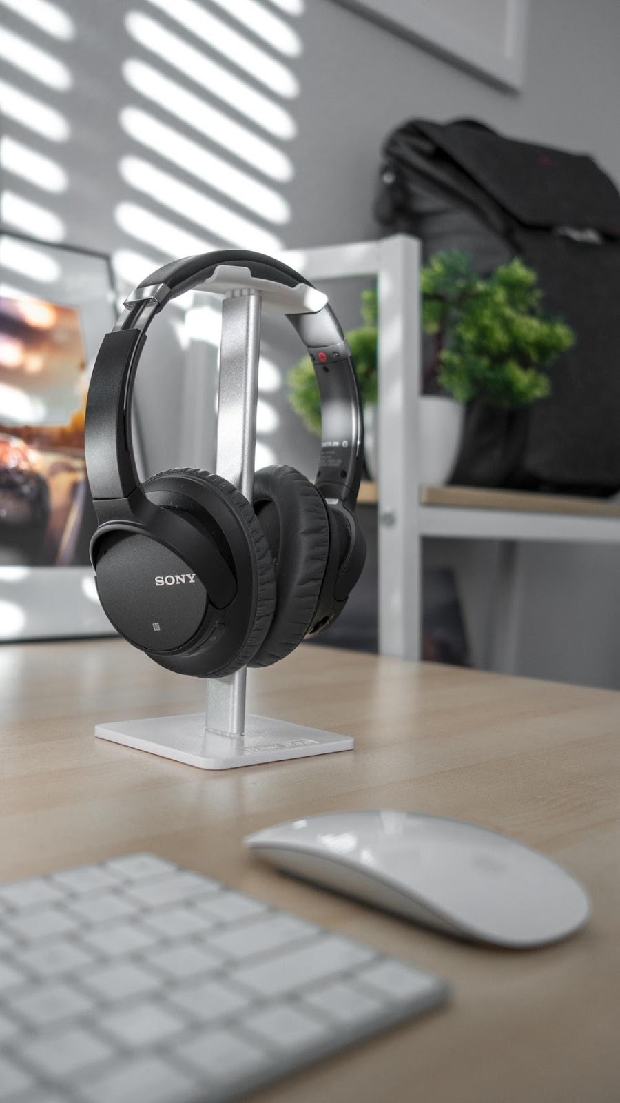 black Sony headphones hung on stand near Apple Magic Keyboard and Mouse
