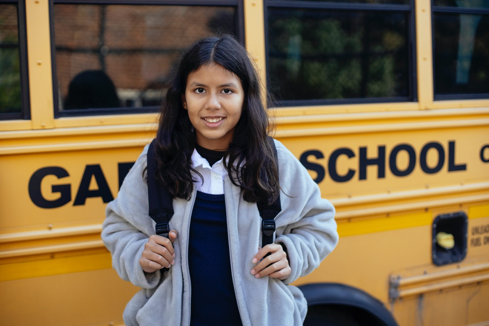A young girl stands in front of a school bus while wearing a backpack.