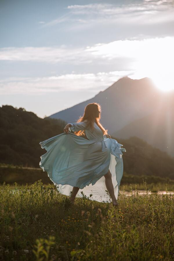 Foto de uma mulher em um campo aberto com um vestido azul claro longo, dançando sob o Sol.