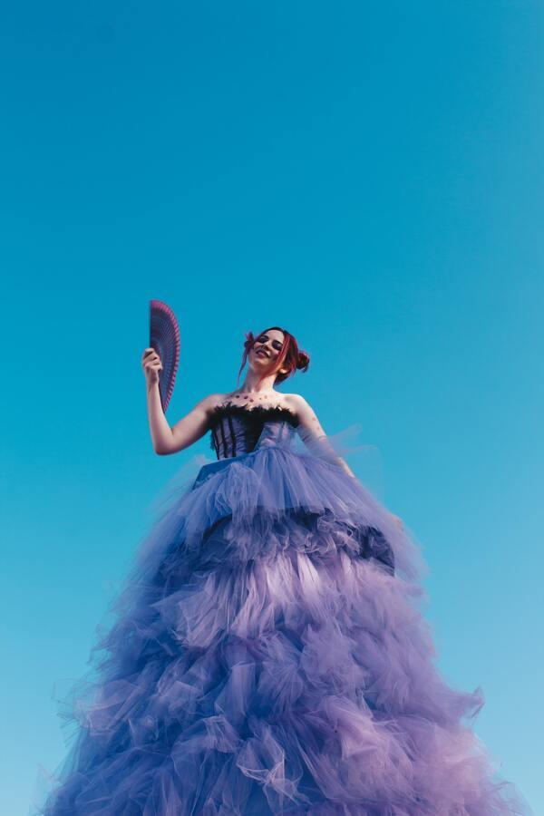 Foto tirada debaixo de uma mulher com um vestido roxo cheio de babado segurando um leque.