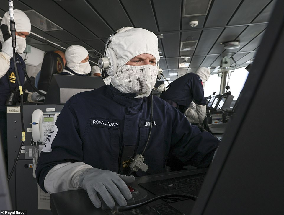 Battle stations: Officers and crew in white anti-flash balaclavas and mittens feel the pressure yesterday as they dictate naval operations from Defender¿s bridge