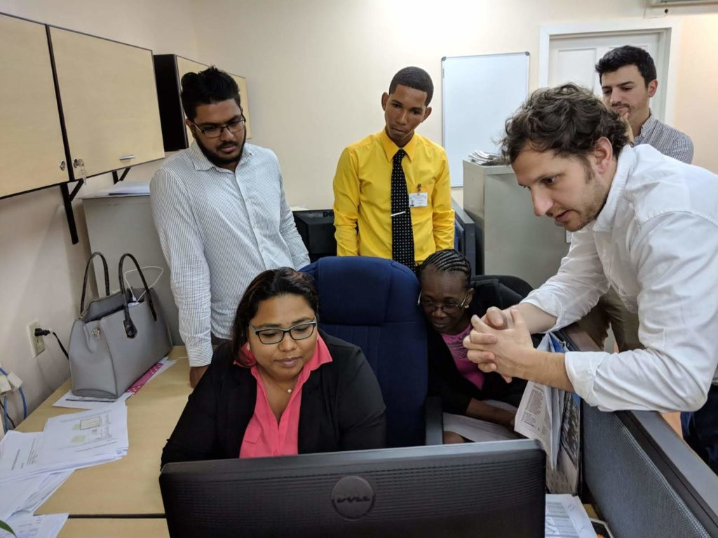 A small group of people are gather around a computer for training session in GIS techniques.