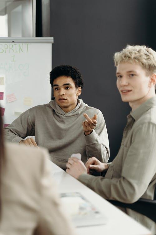 Man in Gray Turtleneck Sweater Sitting Beside Boy in Gray Sweater