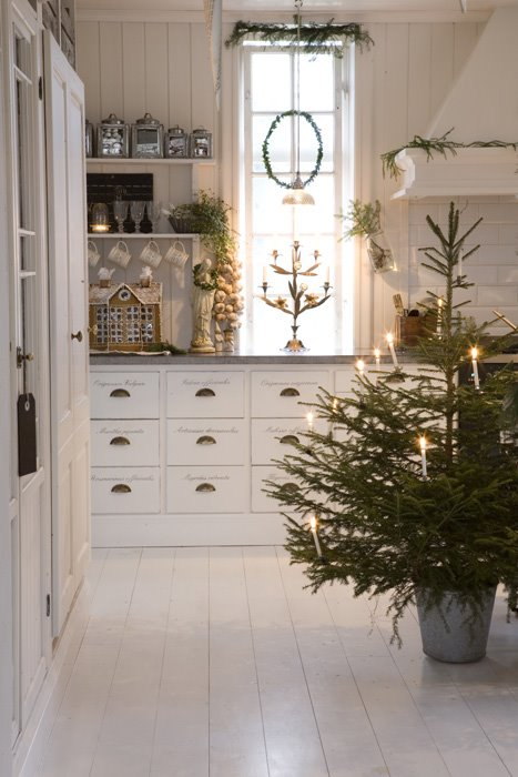 country farmhouse white kitchen with rustic christmas decor and a mini christmas tree with twinkle lights