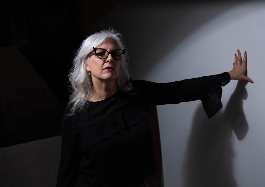 Woman standing sideways with arm on wall appearing to have anxiety and wondering about a cure