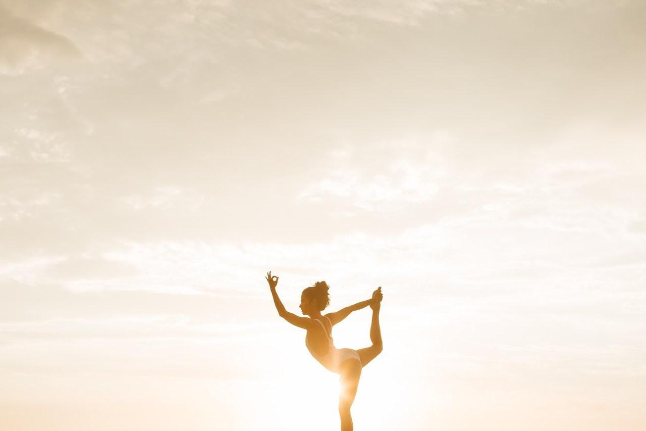 a woman doing an advanced one leg stand in the sunset