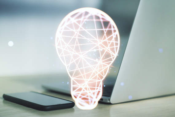 Digital rendering of lightbulb next to computer