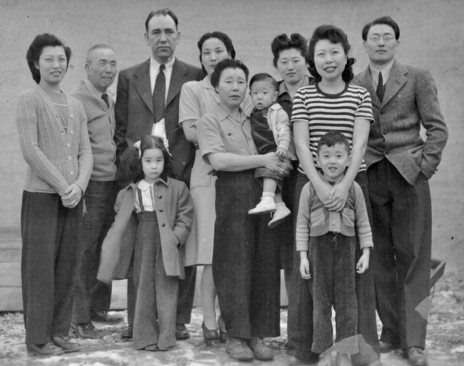 Group photo of Nobuko Miyamoto's family in 1945. They are standing together facing the camera, most with slight smiles. Nobuko appears as a smile child standing in front of her father.