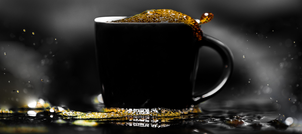 hot coffee sloshing in black cup