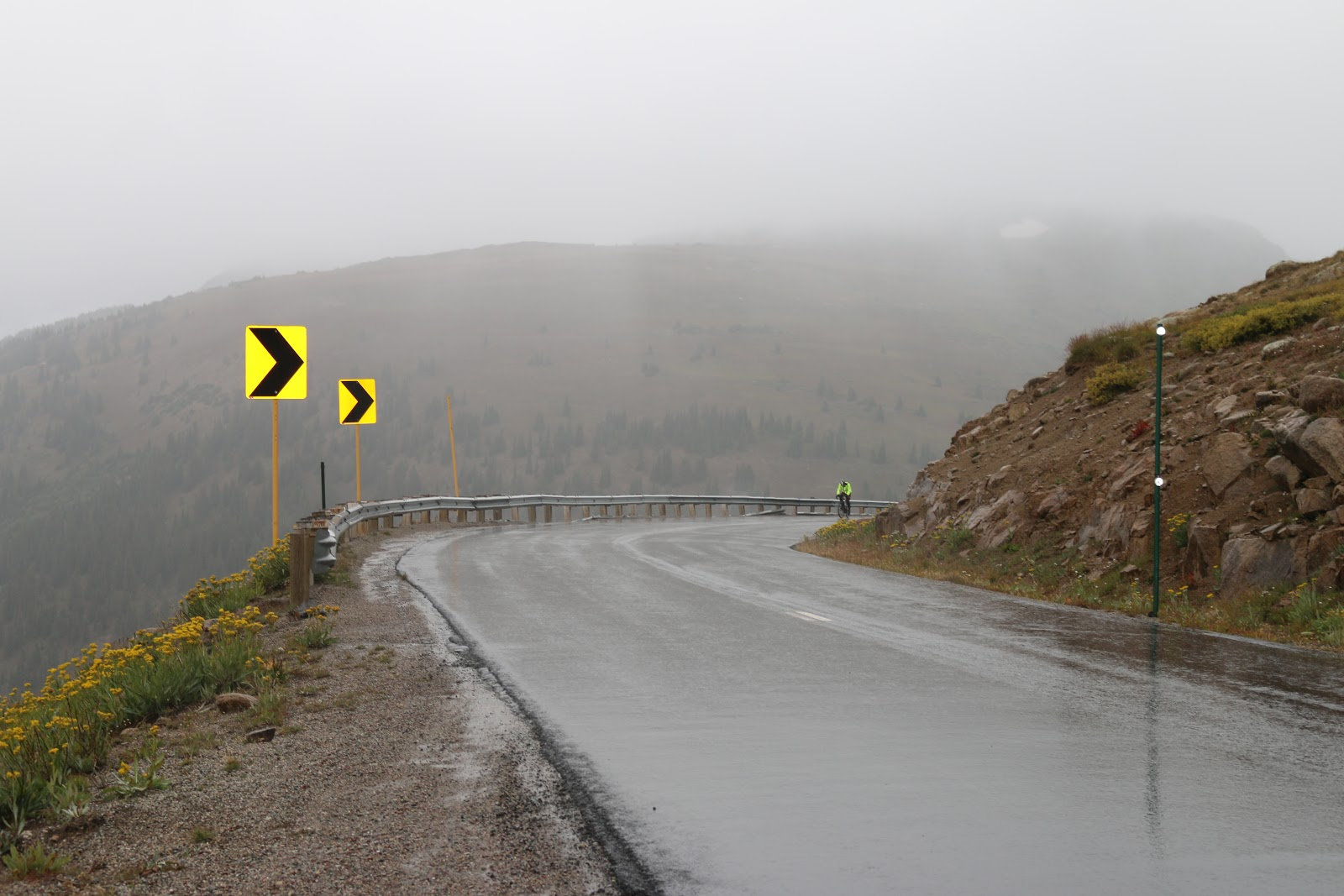 Bicycle climb of Independence Pass - cyclist riding up roadway in rain.