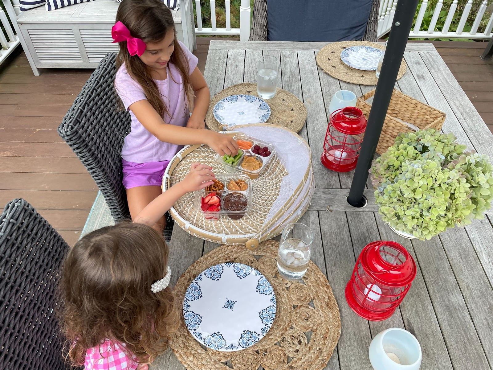 Little girls enjoying snacks on the deck in summer protected by Modern Pest