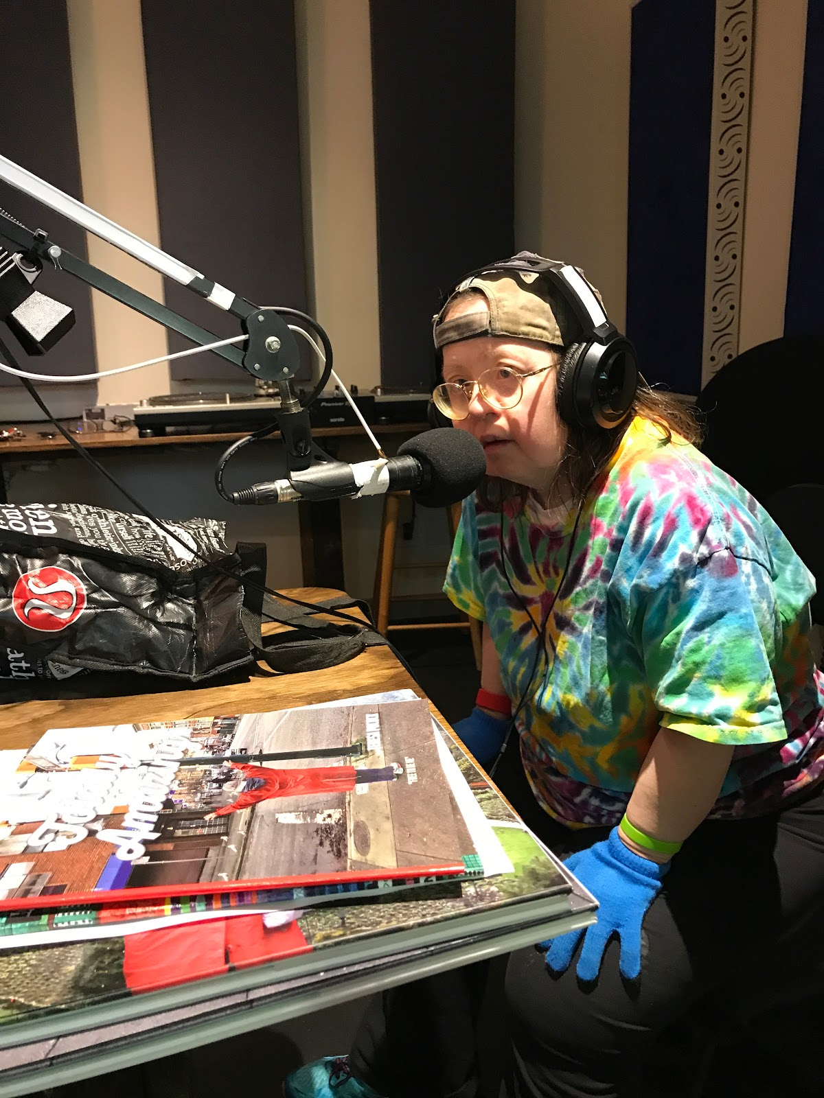 Teresa Pocock wears headphones and leans toward the microphone in a radio interview with Cathy Browne for CO-OP Radio on July 24, 2019. Photo by Franke James.