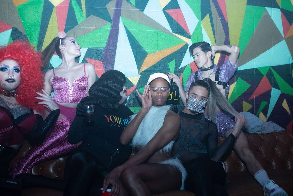 Group of six people posing for a picture at a queer event showing off their Drag, wigs, and pink leopard print and more.