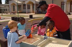 teacher guiding preschoolers in outdoor activity.