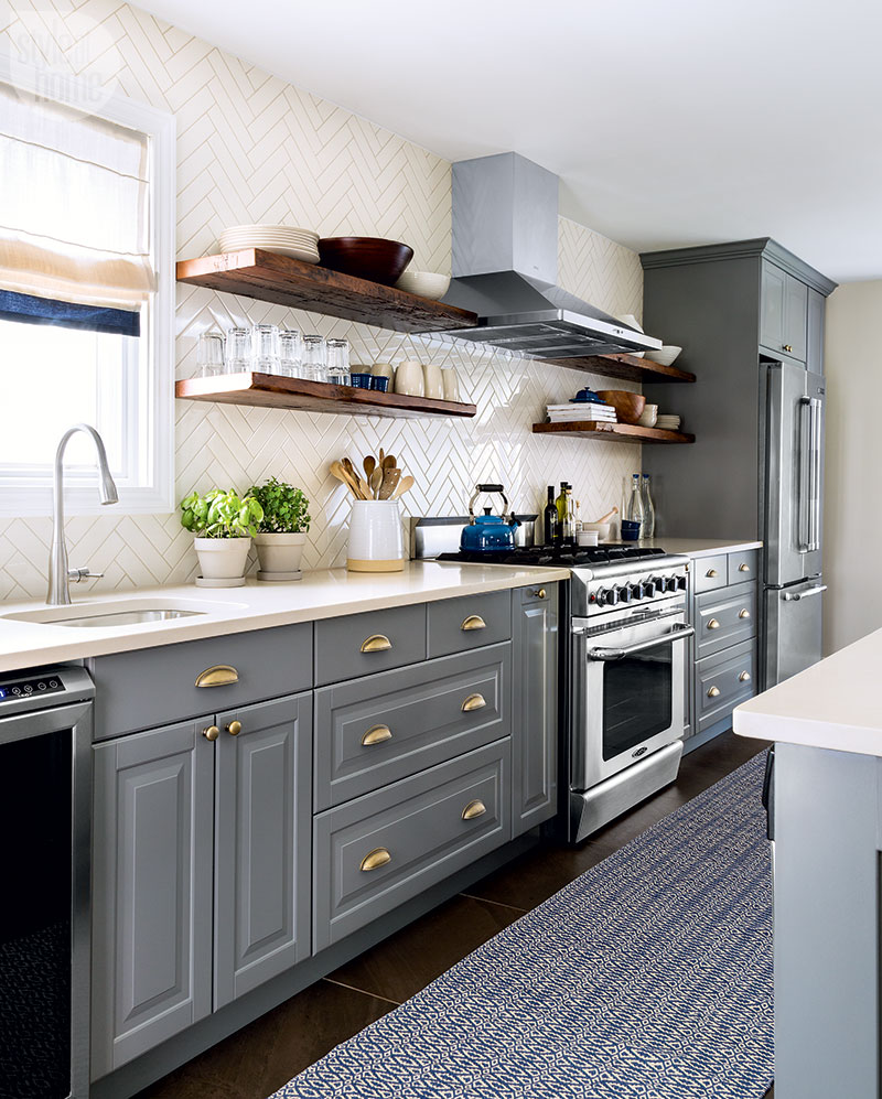 modern galley kitchen with grey cabinets, white herringbone backsplash, brass cabinet hardware, wooden open shelves and stainless steel appliances