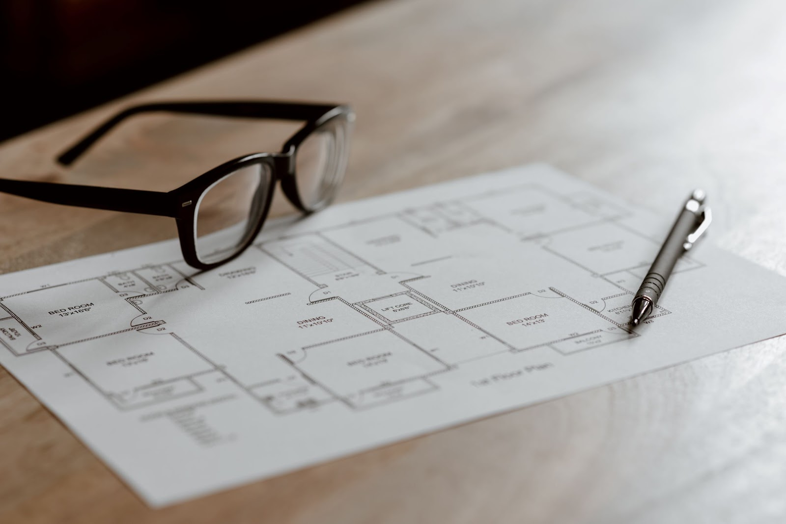 glasses laying on top of house floor plan