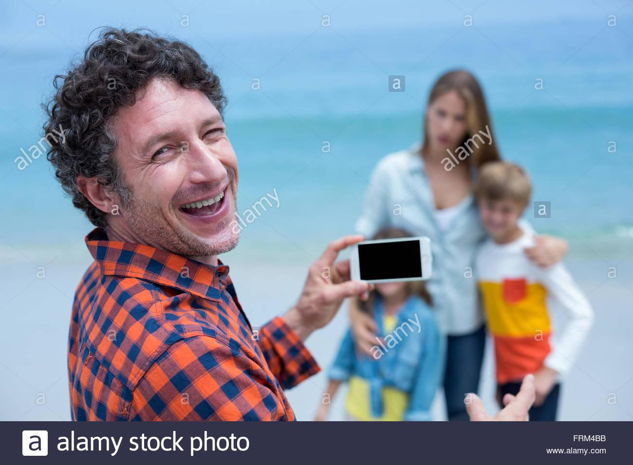 Happy father photographing family with cellphone at beach Stock Photo -  Alamy