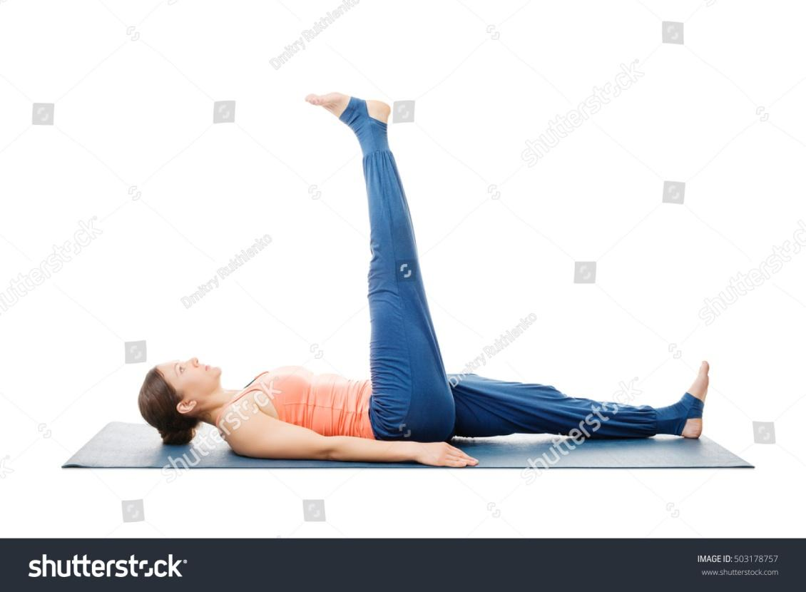 Woman doing yoga asana Uttanpadasana - lying down straight leg raise pose posture isolated on white background