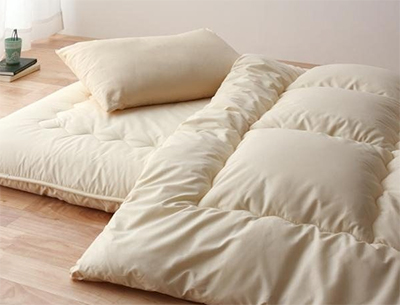 A japanese style woolen floor futon mattress offers comfort and is designed for floor-use. Image from thebedlyft.com.