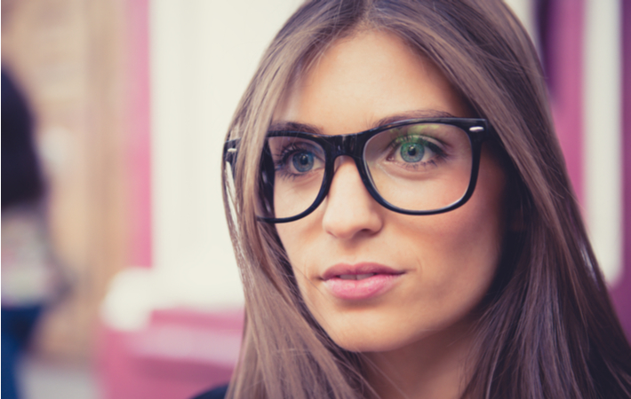 woman with glasses slightly smiling