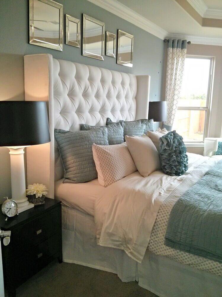 Cama de casal com cabeceira estofada branca, parede cinza claro espelhos em cima da cabeceira e decoração em tons cinza e branco.