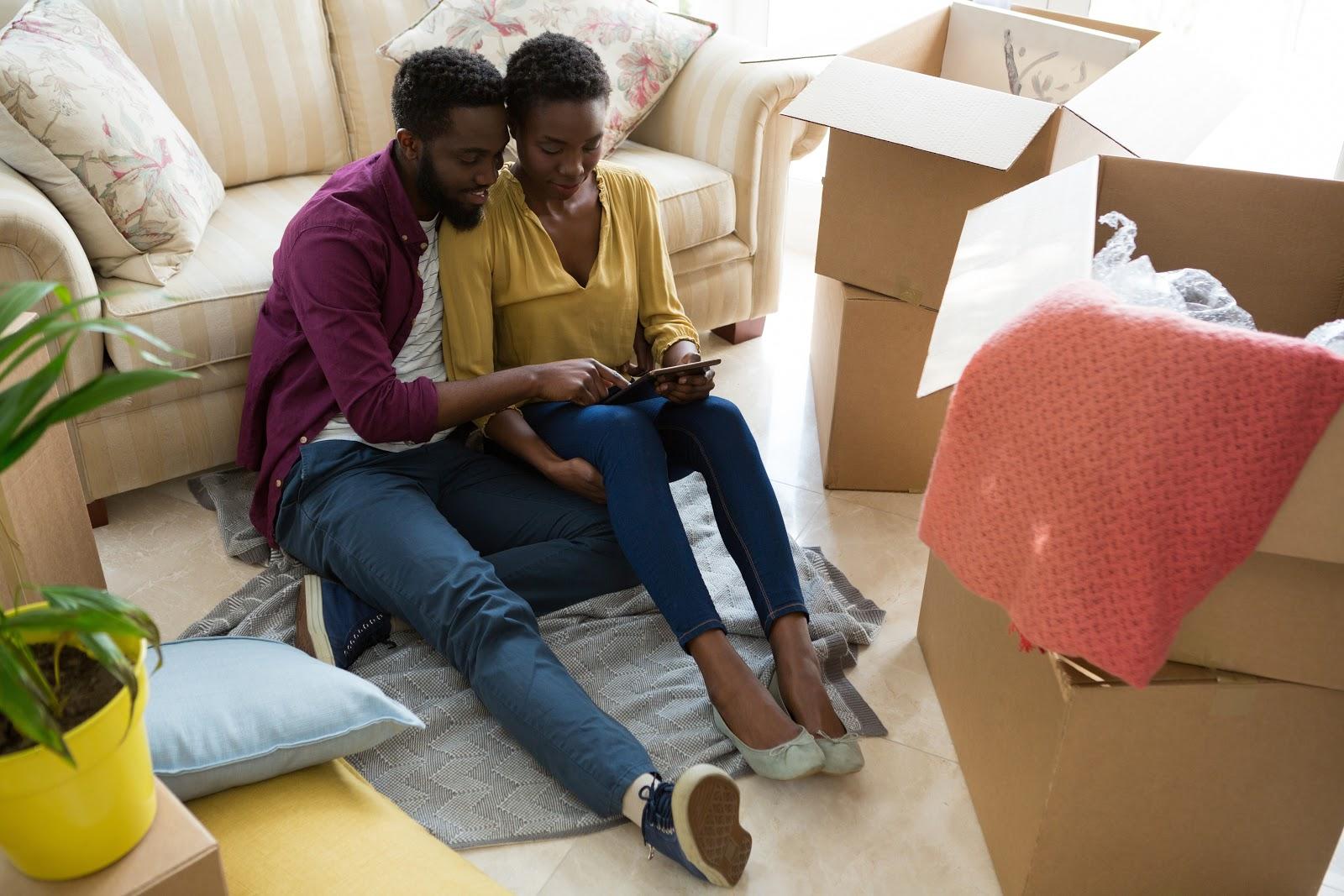 Um casal mexendo em um tablet.