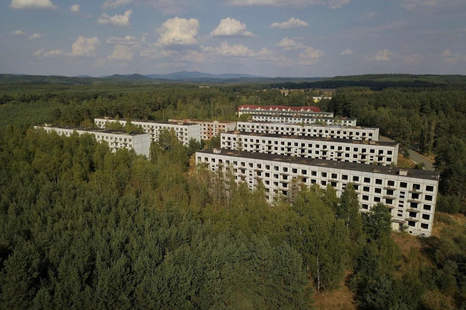 Заброшенные пятиэтажки в Ральско неподалеку от бывшей советской авиабазы. На заднем плане — отремонтированные дома