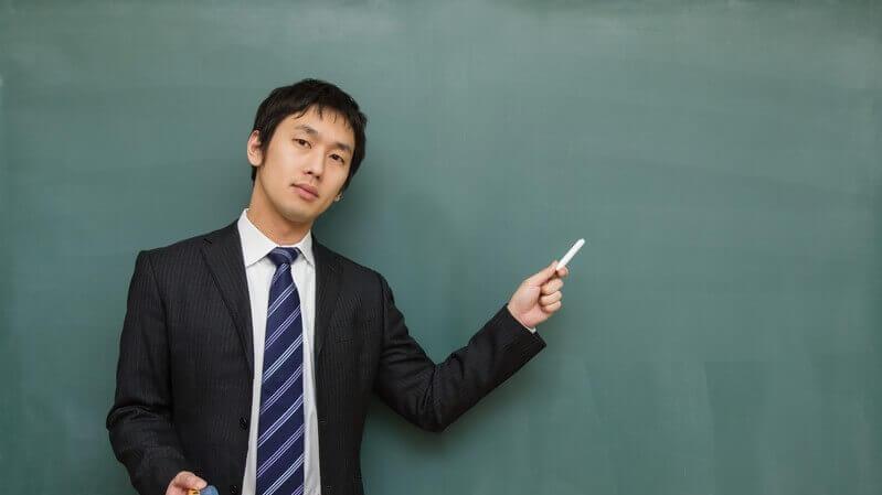 黒板の前で解説する男性の写真。