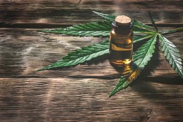 Cannabis essential oil in the vial with a green leaf on a wooden table background with a copy space. Herbal medicine concept.