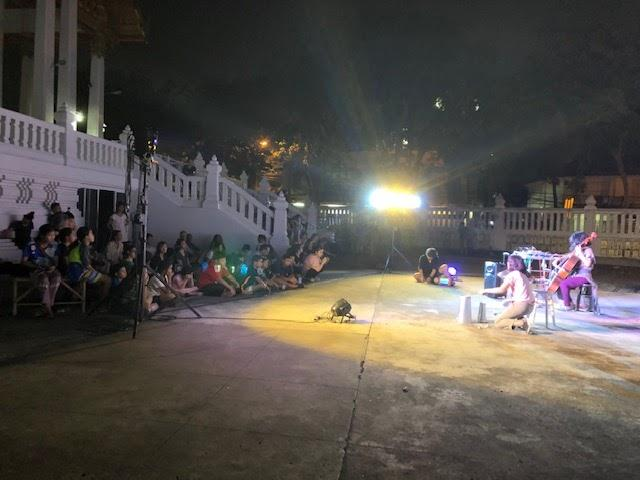 A group of people performing on stage in front of a building  Description automatically generated