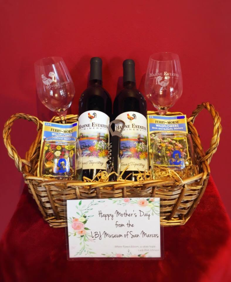 "Two bottles of Hahne Estates Winery's signature wine: Texas Tapestry, two long stem Hahne Estates Winery wine glasses, two Claudia Taylor ""Lady Bird"" Johnson stemless wine glasses, two wildflower seed packets, one cork screw."