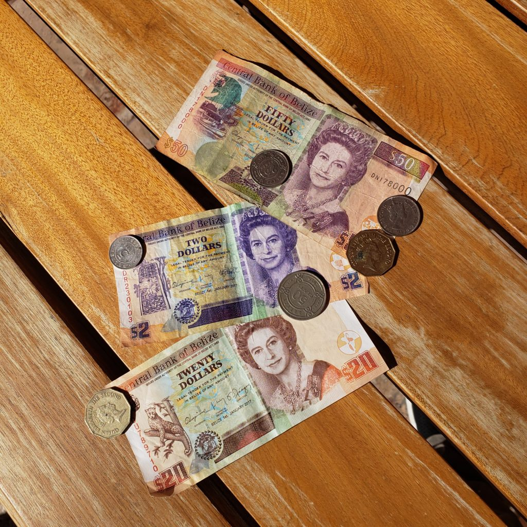 Belizean notes and coins on a wooden table