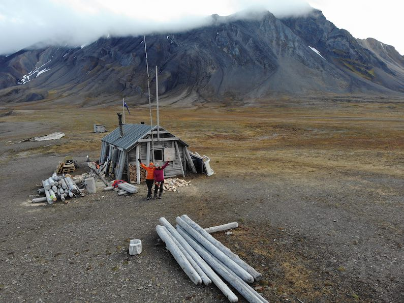 Hilde Fålun Strøm (left) and Sunniva Sorby (right) standing in front of the trapper cabin 'Bamsebu' in Svalbard, Norway.