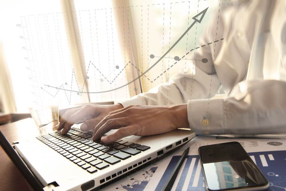 Business man typing on laptop with illustrative data elements