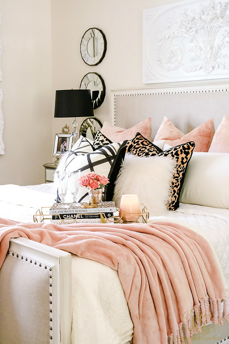 Glamour bedroom setting. White bedding with pink throw pillows and blanket with accents of leopard pillows and fuzzy white pillows.