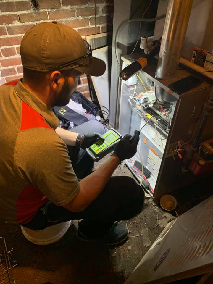 HVAC technician wears rubber gloves and performs a diagnostic test on a home unit