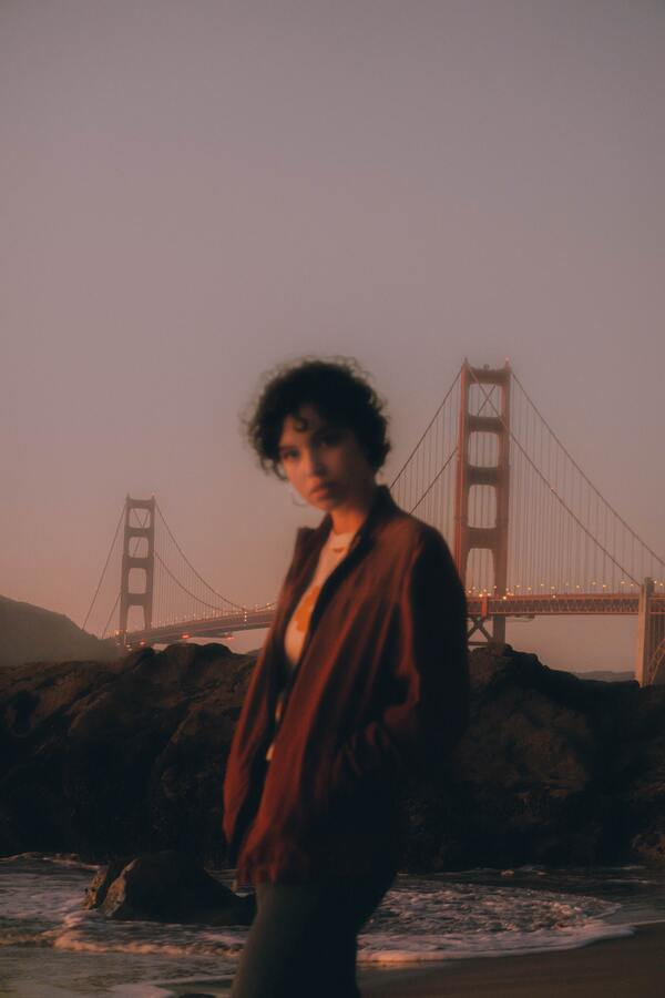 foto embaçada de uma mulher de cabelo curto em frente a ponte de São Francisco